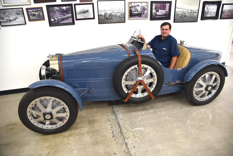 man seated in vintage race roadster