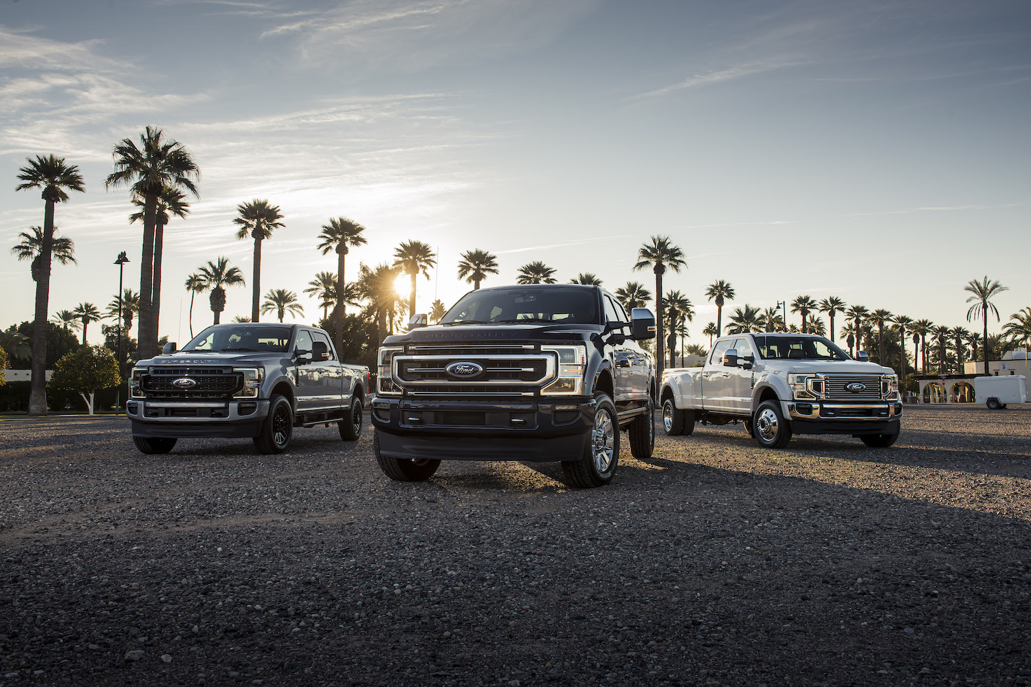 three super duty trucks in front of palm trees