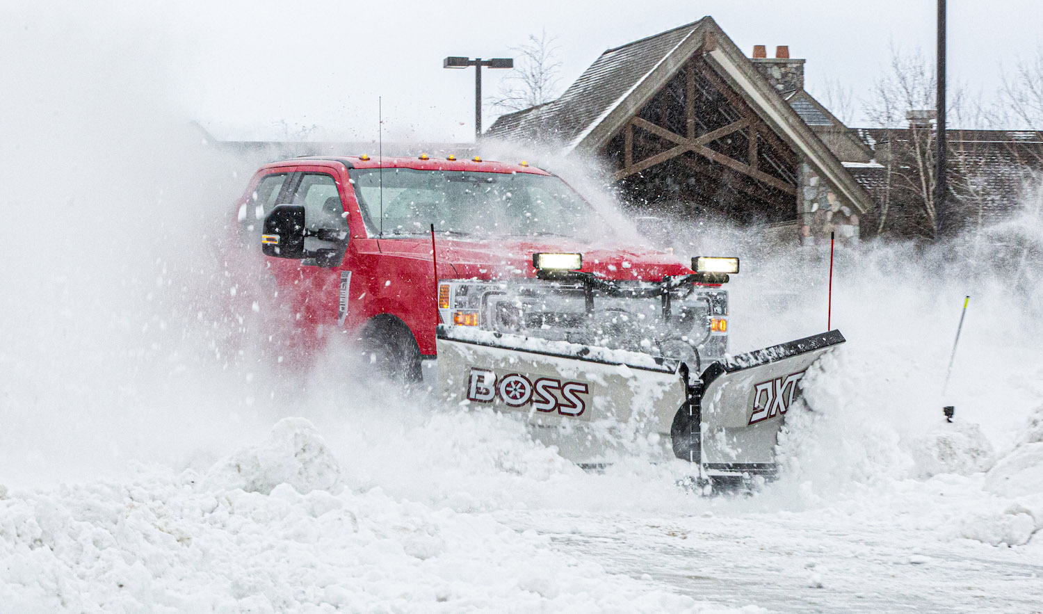 red super duty with boss plow in snow action front three-quarter