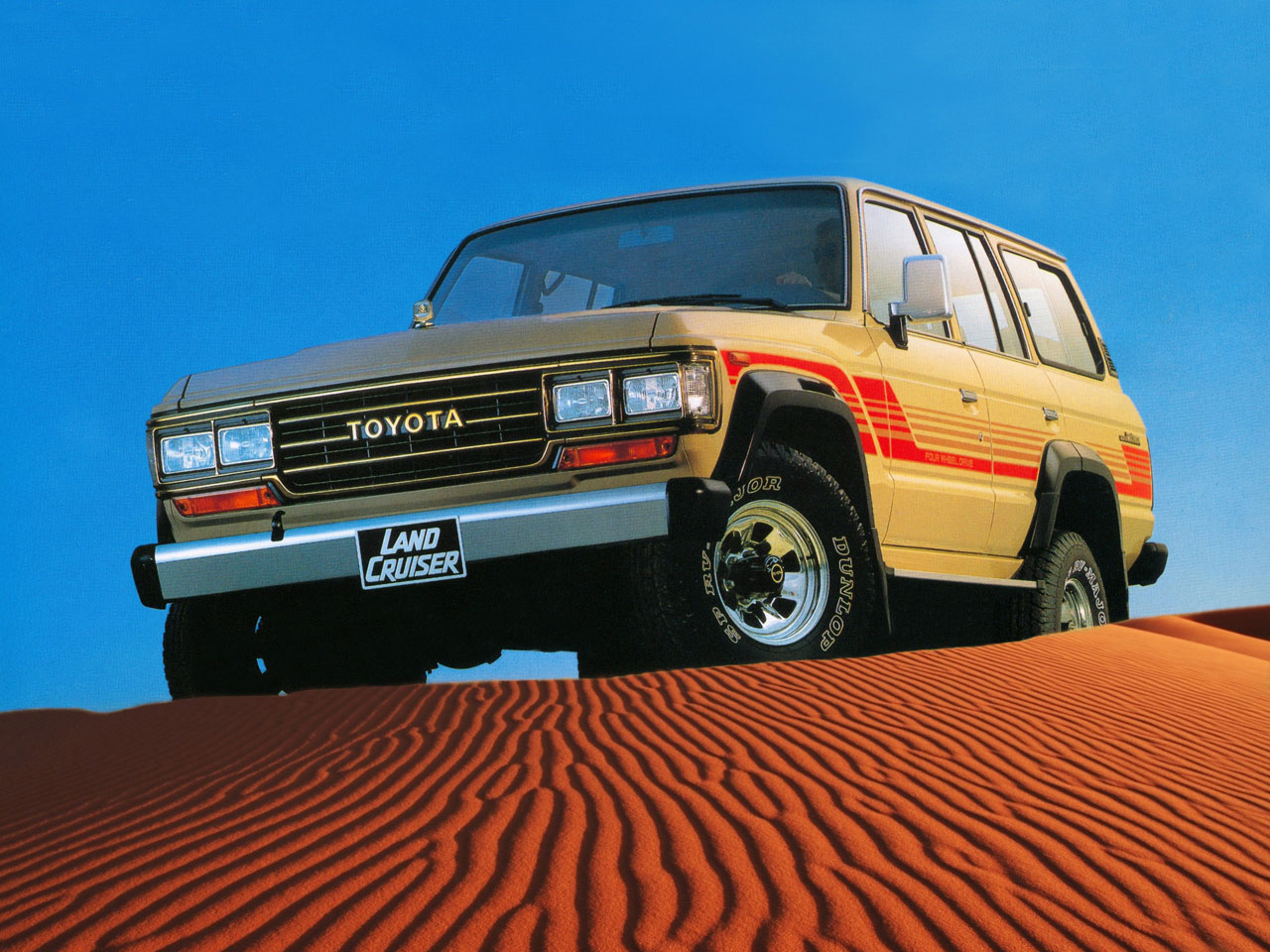 1987 Toyota Land Cruiser FJ60 on top of a sand dune