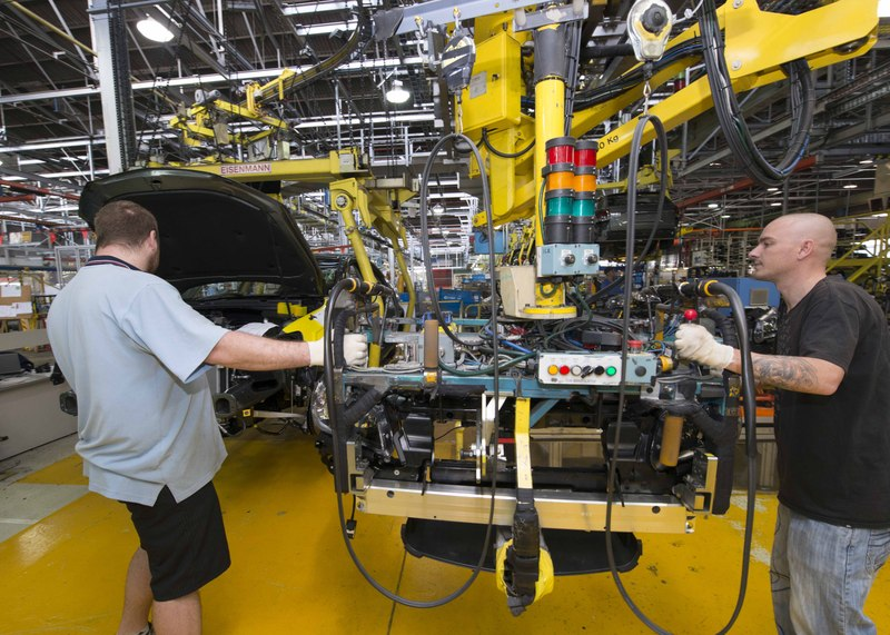 manufacturing line workers operate robotic arm