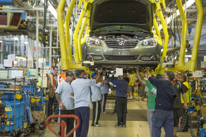 assembly line workers check holden sedan on lift