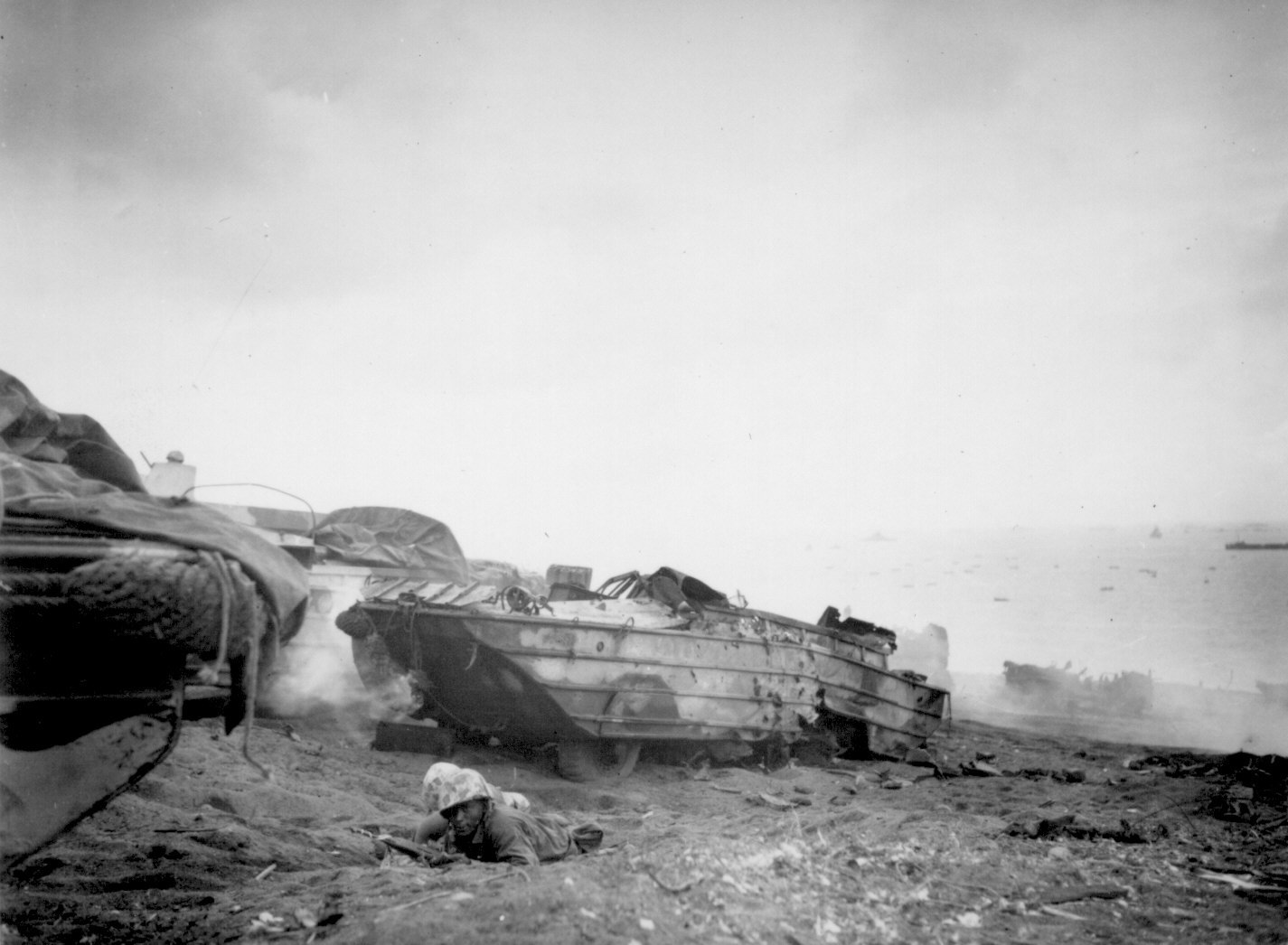 two marine corps men on iwo jima beach with destroyed duck in background