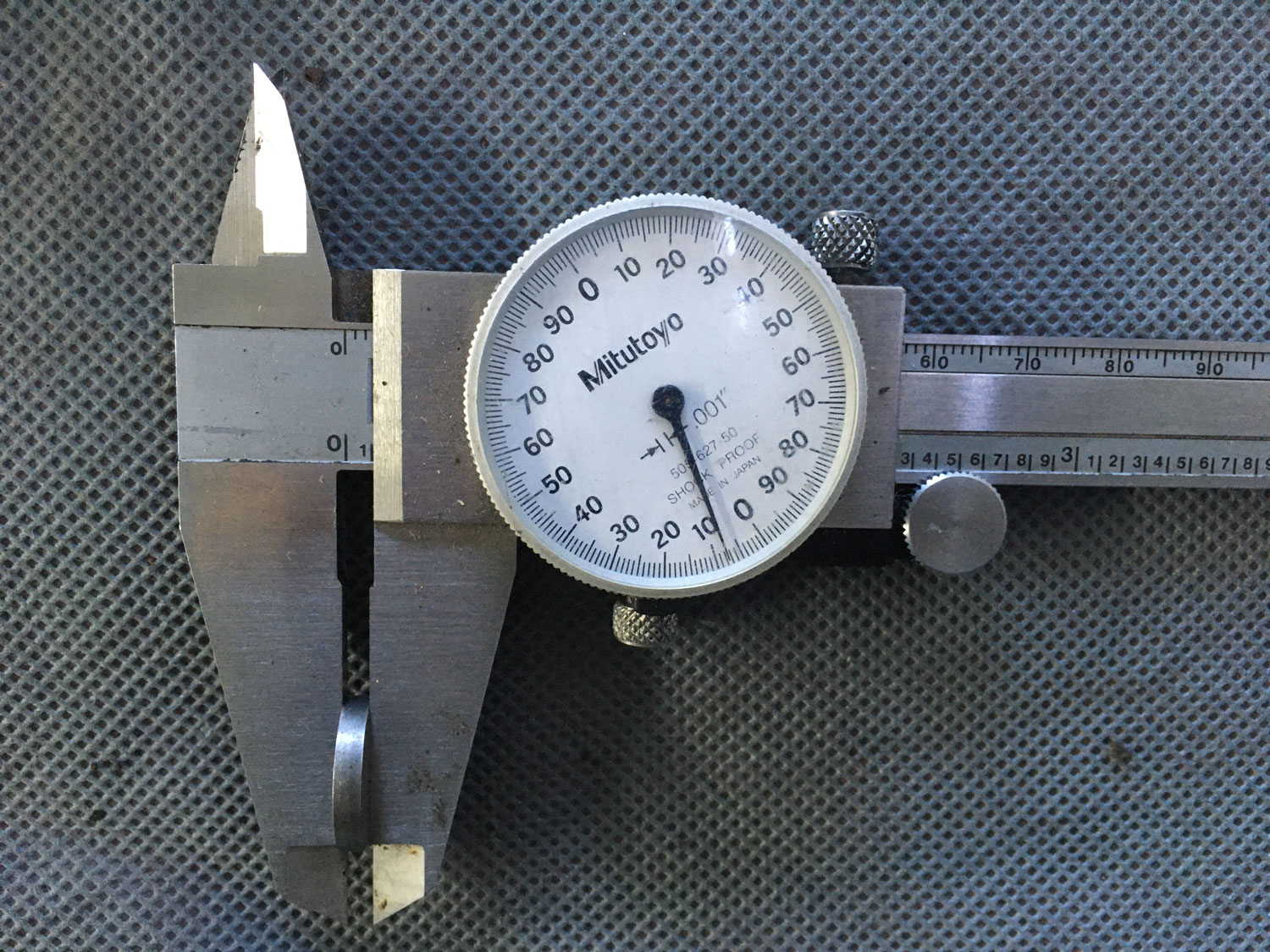 The calipers measure the thickness across the entire shim, and the dial really can only be read to the thousandth of an inch.