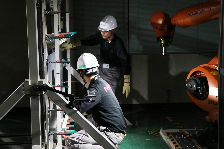 nissan employee technicians adjust steel panel