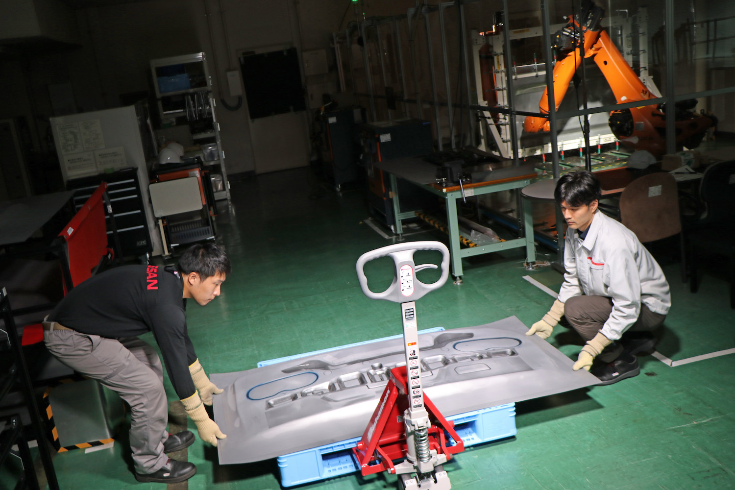 two nissan employees carry steel part