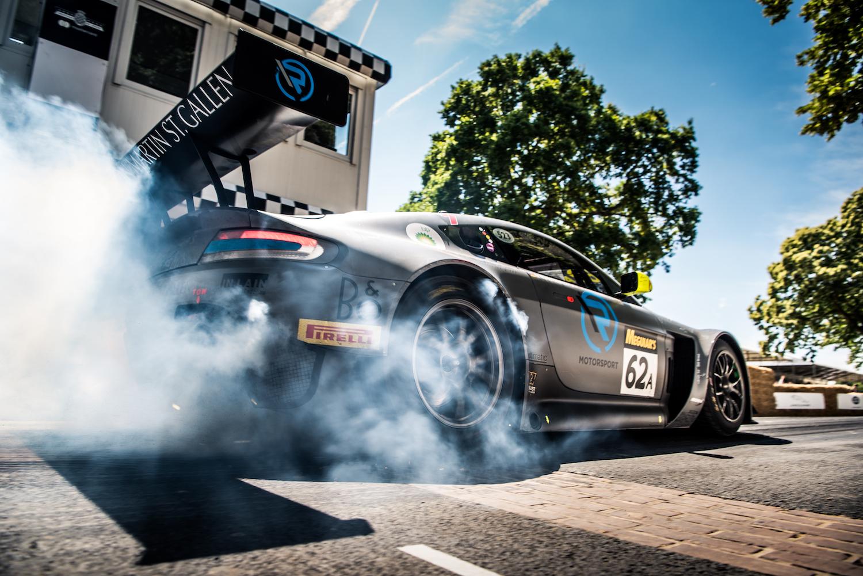 aston martin rear three-quarter track car spinning tires
