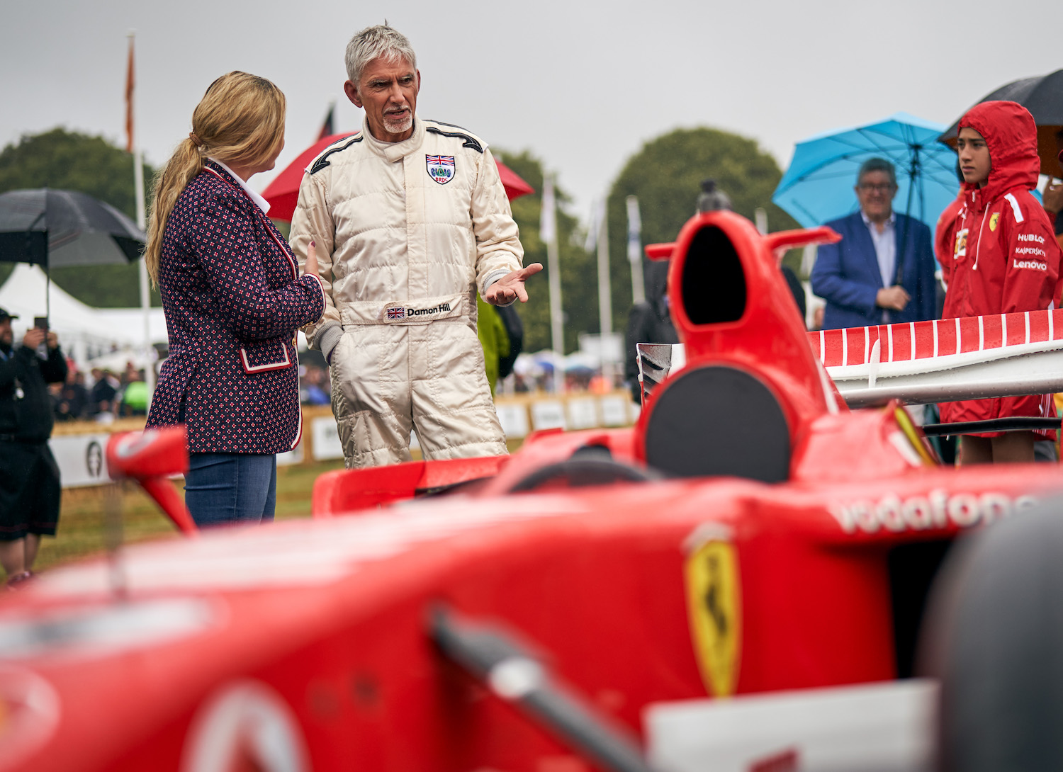 race car driver chatting with woman at goodwood festival of speed